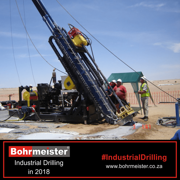industrial oil drilling with men standing around it